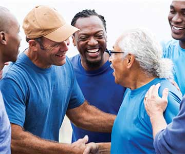Group of smiling men wearing blue shirts are shaking hands with one another in support